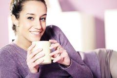 Jonge vrouw die een kop van koffie i houdt Stock Afbeeldingen
