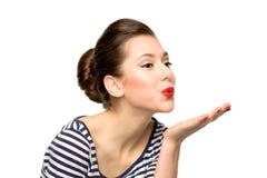 Jonge vrouw die een kus blaast Stock Foto