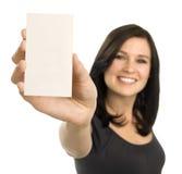 Jonge vrouw die een leeg adreskaartje houdt Stock Fotografie