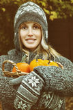 Jonge vrouw die een mand pompoenen houden Stock Afbeeldingen