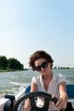 Jonge vrouw die een motorboot drijft stock foto