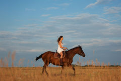 Jonge vrouw die een paard berijdt Royalty-vrije Stock Afbeeldingen