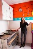 Jonge vrouw die een pan houden en op iemand richten terwijl status royalty-vrije stock afbeelding