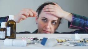 Jonge vrouw die een pil houden en lookng bij het stock videobeelden