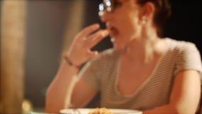 Jonge vrouw die een plak van pizza eten stock videobeelden