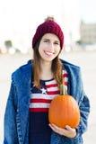 Jonge vrouw die een pompoen houden Stock Afbeelding