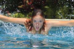 Jonge vrouw die in een pool zwemt Royalty-vrije Stock Afbeeldingen