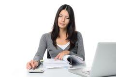 Jonge vrouw die een rapport of rekeningen controleren Stock Afbeeldingen