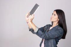 Jonge vrouw die een selfie met tabletcomputer nemen die op gre wordt geïsoleerd Royalty-vrije Stock Foto's