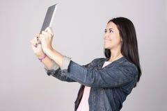Jonge vrouw die een selfie met tabletcomputer nemen die op gre wordt geïsoleerd royalty-vrije stock afbeelding