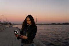 Jonge vrouw die een selfie nemen die een ringsflits gebruiken als vullingslicht bij een zonsondergang met een mening over rivier  stock foto