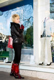 Jonge vrouw die een show-venster van winkel onderzoekt stock foto