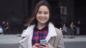 Jonge vrouw die een slimme telefoon wegknippen stock video