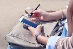 Jonge vrouw die een smartphone houden Stock Foto