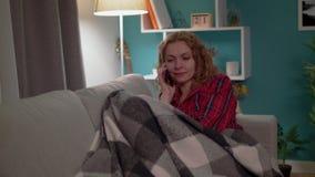 Jonge vrouw die een smartphone op een bank in comfortabele woonkamer in de avond uitnodigen stock video