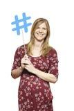 Jonge vrouw die het sociale media teken glimlachen houden Stock Afbeeldingen