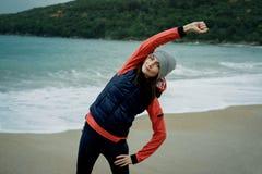 Jonge vrouw die een sportenvest dragen die door de winteroverzees uitoefenen Stock Foto