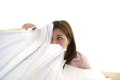 Jonge vrouw die in een stapel documenten kijkt Stock Foto's