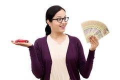 Jonge vrouw die een stuk speelgoed auto en een Indische munt houden Royalty-vrije Stock Afbeelding