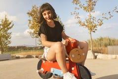 Jonge vrouw die een stuk speelgoed motorfiets in speelplaats berijden stock fotografie