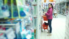 Jonge vrouw die in een supermarkt winkelt stock videobeelden