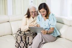 Jonge vrouw die een tablet met haar moeder gebruiken royalty-vrije stock foto