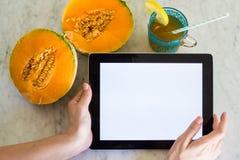 Jonge vrouw die een Tablet met het modelscherm houden met handen op een lijst met de zomerfruit en drank Stock Afbeelding