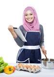Jonge vrouw die een tablet voor lezingsrecept gebruiken voor het maken van een maaltijd royalty-vrije stock afbeeldingen