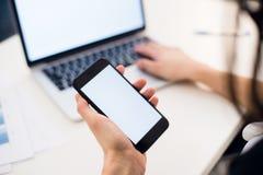 Jonge vrouw die een telefoon houden Werkplaats dichtbij het venster met laptop Sluit omhoog royalty-vrije stock foto's