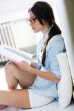 Jonge vrouw die een tijdschriftzitting op de vloer lezen stock fotografie