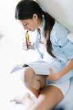 Jonge vrouw die een tijdschriftzitting op de vloer lezen royalty-vrije stock foto