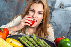 Jonge Vrouw die een Tomaat bijten Stock Afbeeldingen