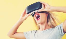 Jonge vrouw die een virtuele werkelijkheidshoofdtelefoon met behulp van stock foto's