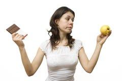 Jonge vrouw die een voedseldilemma heeft stock afbeeldingen