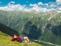 Jonge vrouw die in een weide met bloemen voor de bergketen Noord- van de Kaukasus liggen Royalty-vrije Stock Afbeeldingen