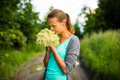 Jonge vrouw die elderflower plukken Stock Foto's