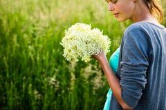 Jonge vrouw die elderflower plukken Stock Afbeelding