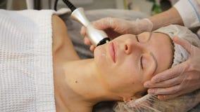 Jonge vrouw die elektrische gezichtsmassage ontvangen stock videobeelden