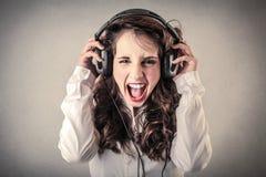 Jonge vrouw die en aan de muziek gillen luisteren stock afbeeldingen