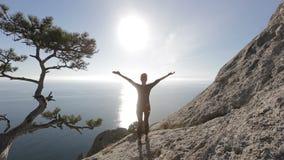 Jonge vrouw die en de bovenkant van een berg beklimmen bereiken Dame op de top in mooi landschap die de kust onder ogen zien stock footage