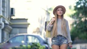 Jonge vrouw die en in de stad lopen winkelen stock footage