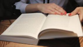 Jonge vrouw die en een boek in comfortabele koffie openen lezen Bedrijfsdame die een boek lezen Sluit omhoog mening Het bestudere stock video