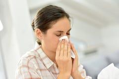 Jonge vrouw die en haar neus blazen niezen Royalty-vrije Stock Foto