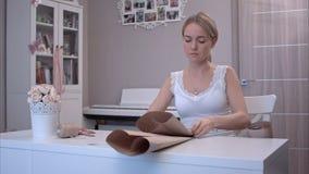 Jonge vrouw die en het snijden verpakkend document vouwen stock afbeeldingen