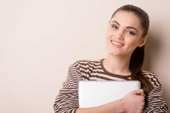 Jonge vrouw die en laptop bevinden zich houden Stock Foto's