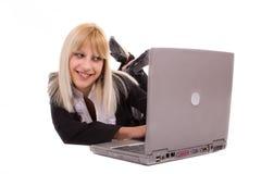 Jonge vrouw die en laptop ligt bekijkt Stock Afbeelding
