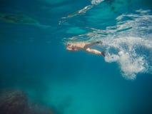 Jonge vrouw die en met masker en vinnen in duidelijk blauw water zwemmen snorkelen royalty-vrije stock afbeeldingen