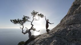 Jonge vrouw die en op een berg dansen lopen Dame op de top in mooi landschap boven het overzees stock videobeelden