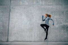 Jonge vrouw die en op stadsstraat lopen springen royalty-vrije stock foto's