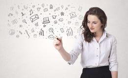 Jonge vrouw die en pictogrammen en symbolen trekken schetsen Royalty-vrije Stock Foto's
